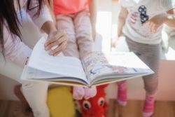 dzieci oglądają książeczkę z panią